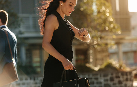 Businesswoman checking time while going to office