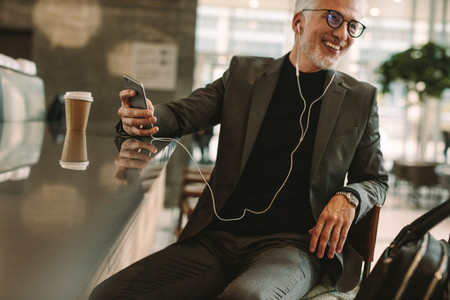 Mature man at coffee shop listening music from phone
