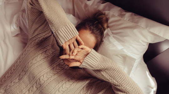 Woman lying on bed with hands covering face