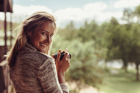 Smiling woman having coffee in morning