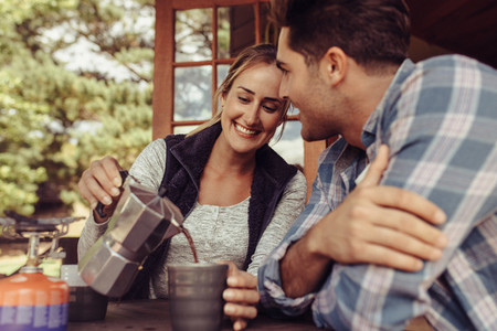 Woman serving coffee to her boyfriend in morning