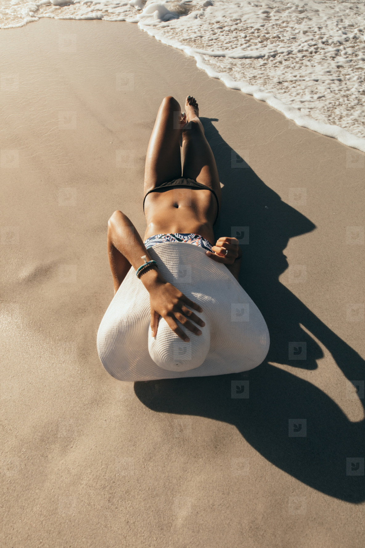 Woman relaxing at the beach wearing sun hat