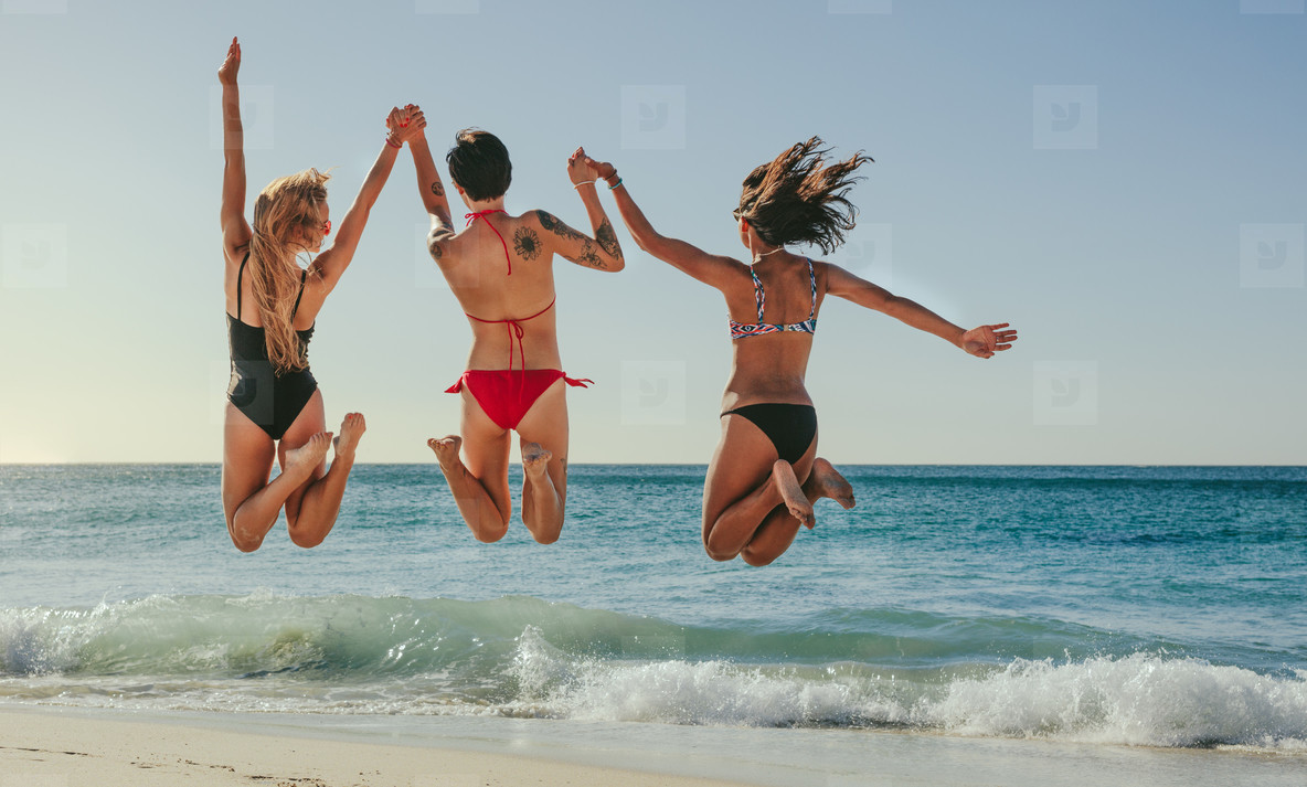 Women jumping in air and enjoying at the beach