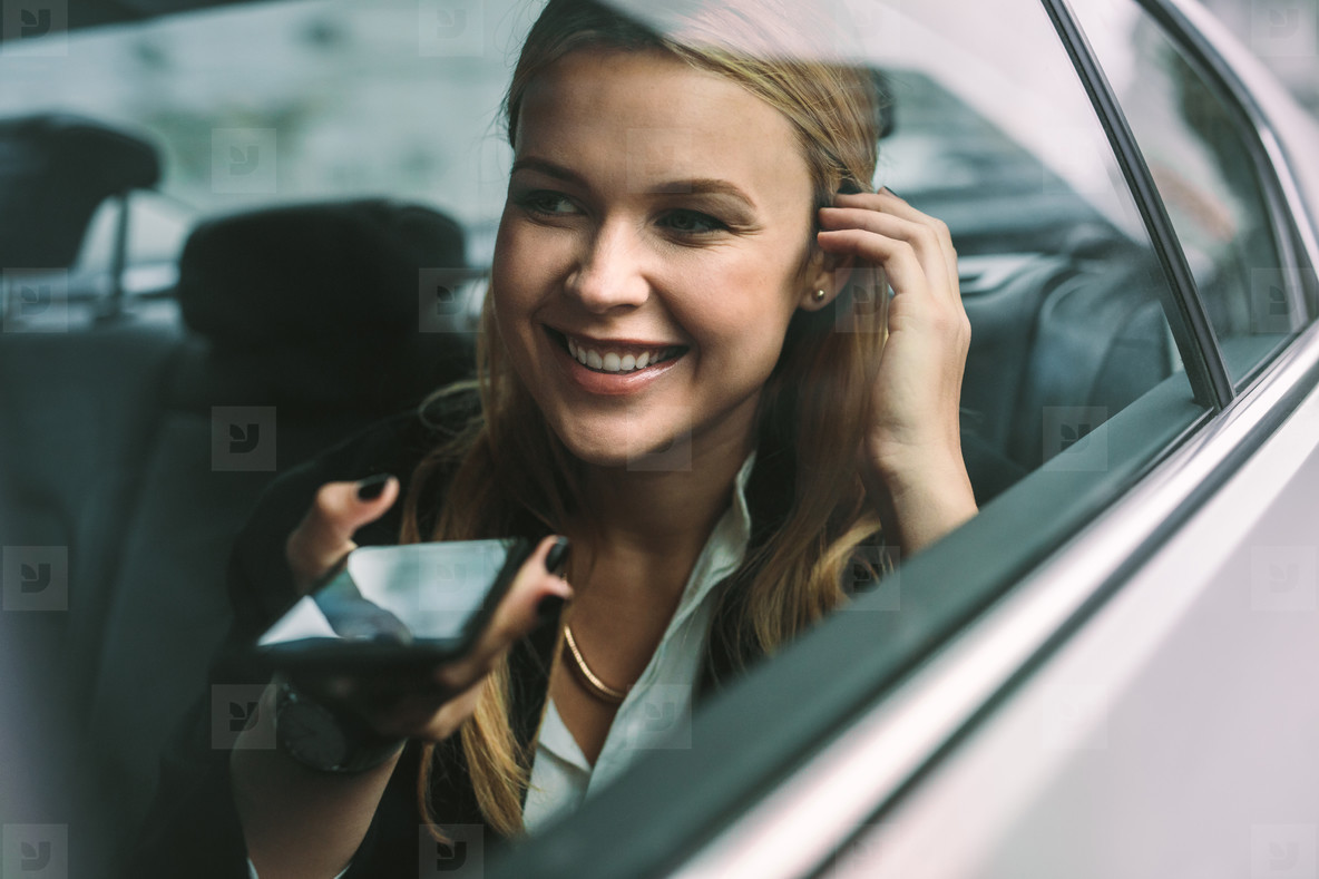 Businesswoman making phone call in cab