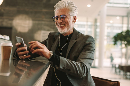 Mature businessman using phone at cafe