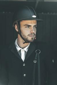 Portrait of young horse rider in barn door wearing helmet and looking at horizon
