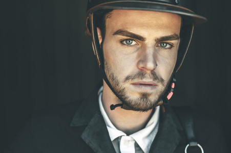 Close portrait of blue eyed horse rider in barn door wearing helmet and looking at camera