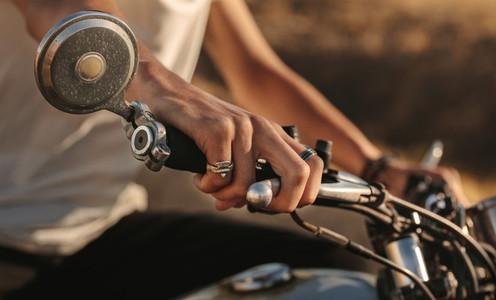 Riders hand on the motorcycle handlebar