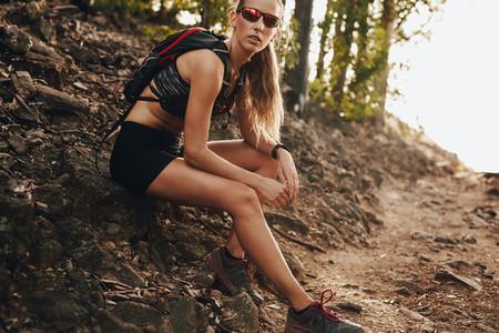 Female runner taking break on trail run
