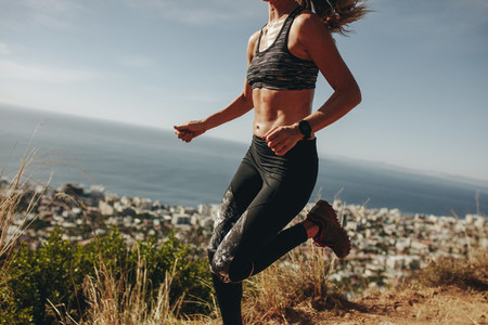 Healthy woman sprinting over mountain trail