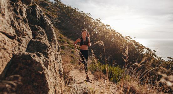 Woman running over extreme terrain on the hillside