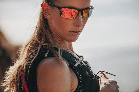 Sporty woman trail runner with sunglasses
