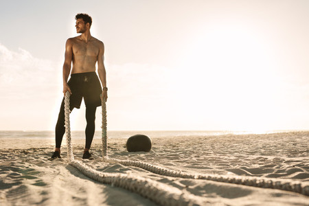 Man standing on the beach holding battling ropes for workout