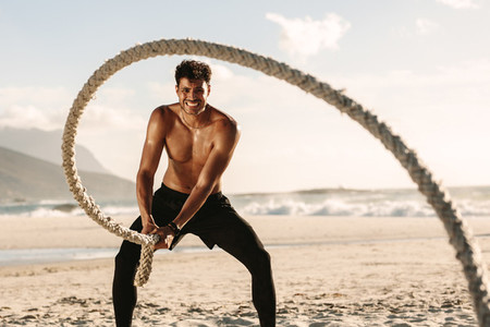 Man doing fitness training at the beach using battling rope