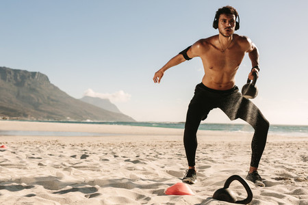 Man doing fitness training at the beach with kettlebells