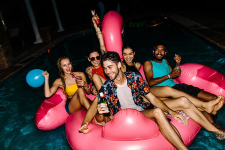 Friends having evening pool party