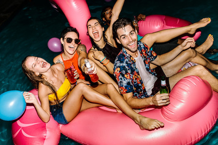 Group of men and women enjoying at pool party