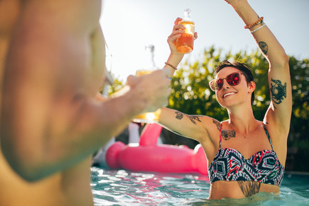 Woman partying with friends in swimming pool