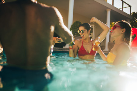 Happy friends making party inside pool