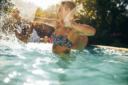 Woman having fun with friends in swimming pool