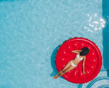 Woman sunbathing on floating mattress in swimming pool