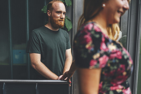 Portrait of young red headed man close to his girlfriend under arquitectural urban structure