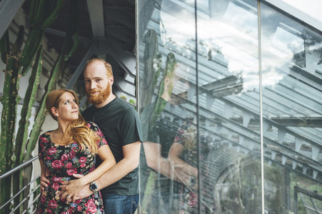 Young red headed couple embraced looking each other in a greenhouse architectural structure