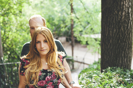 Portrait of young red headed woman close to her couple in an urban garden at sunset
