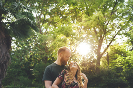 Young red headed couple embraced looking at each other in a urban garden with sun back light