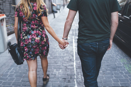 Young couple shaking hands going for a walk in Madrid city streets at dusk