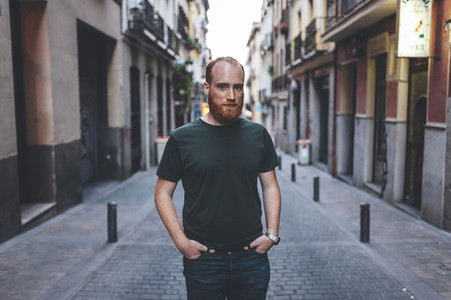 Portrait of confident young red headed man in Madrid city streets at dusk