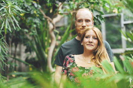 Young red headed couple embraced looking each other in a tropical grarden