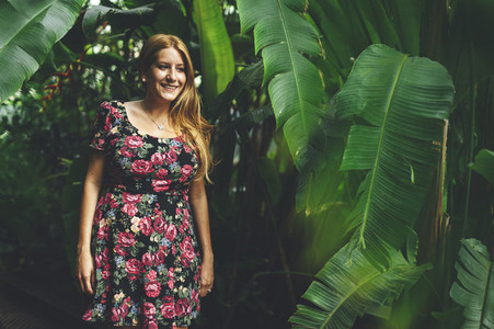 Portrait of confident young red headed woman wearing a flowers dress in a tropical garden