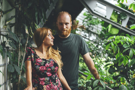 Portrait of young red headed couple looking each other in a greenhouse architectural structure