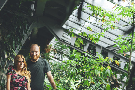 Portrait of young red headed couple looking at camera in a greenhouse architectural structure