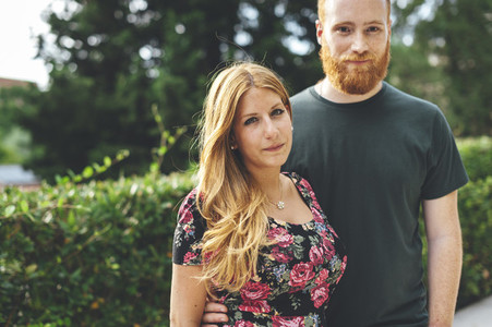 Portrait of young red headed couple in an urban garden at sunset