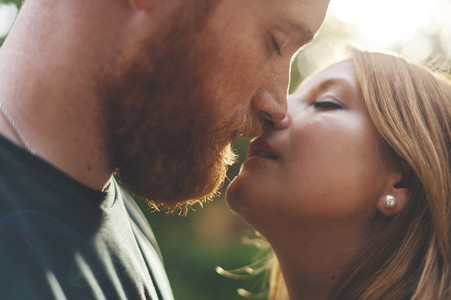 Intimate moment of a red headed couple before kissing and lens flare