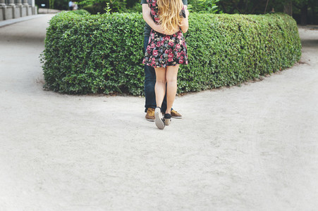Back view of red headed couple embracing in urban garden