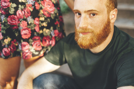 Portrait of red head bearded man with the arm of his girlfriend over the shoulder