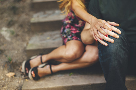 Close up of intimate moment of a couple shaking hands seated in a stairs in the street