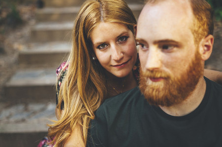 Young red headed woman looking at camera seated in stairs close to her boyfriend