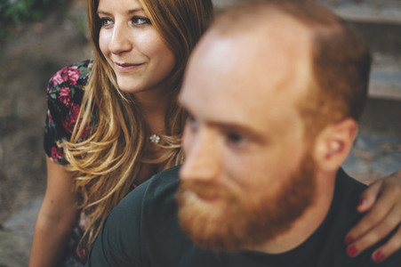 Confident red headed couple seated in the stairs in the street looking a horizon