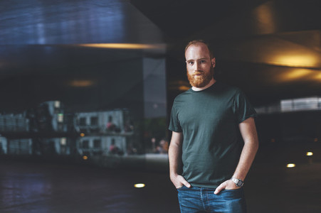Portrait of young red head bearded man in urban scenery