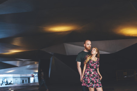 Young couple looking each other under arquitectural urban structure