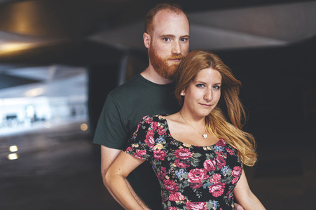 Portrait of young couple under arquitectural urban structure