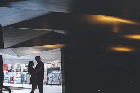 Silhouette of young couple looking each other under arquitectural urban structure