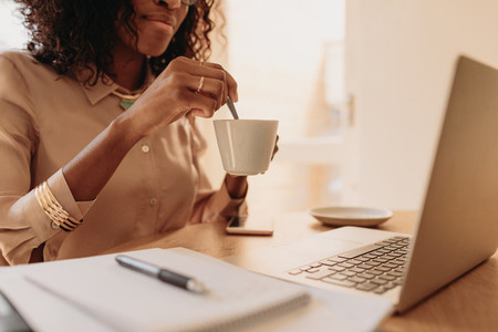 Woman holding a cup of coffee while working on laptop at home