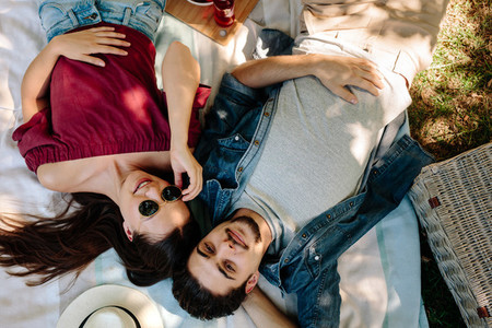 Couple in love lying on picnic blanket