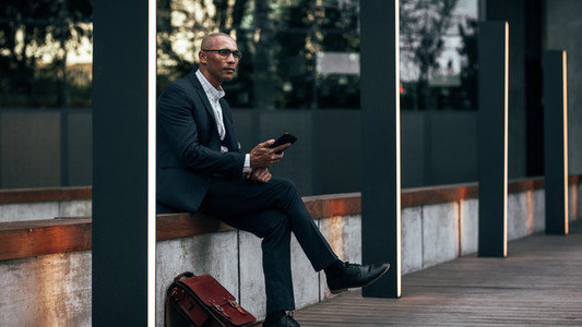 Businessman sitting outdoors holding his mobile phone