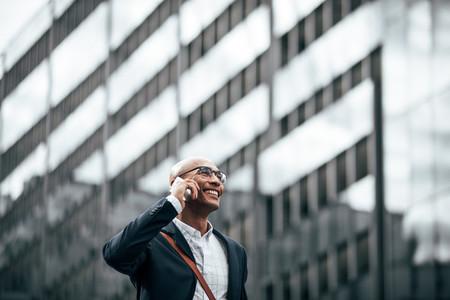 Entrepreneur talking on mobile phone walking outdoors